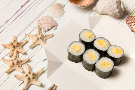 Japanese Tamagoyaki Maki Roll with egg omelet (Tamago) and rice wrapped in nori seaweed on white carton delivery box. Sea shells and stars on wooden background. Stock Photo