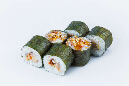 Side view of Japanese Unagi Maki Roll with eel and rice wrapped in nori seaweed, served with sauce and sesame seeds. Close-up of asian traditional dish isolated on background. Isolation menu image