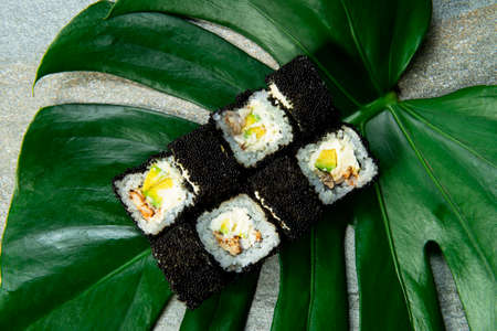 From above of Japanese sushi roll with unagi eel, cream cheese, avocado wrapped in black caviar (flying fish roe Tobiko) served on exotic monstera leaf on gray stone background. food art concept