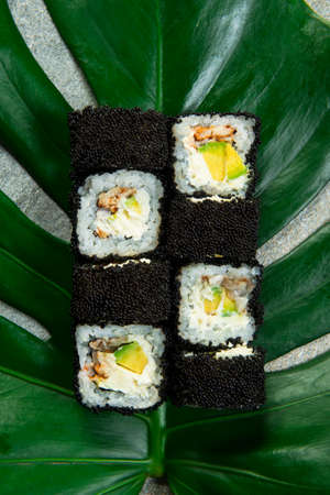Directly above of Japanese sushi roll with unagi eel, cream cheese, avocado wrapped in black caviar (flying fish roe Tobiko) served on exotic monstera leaf on gray stone background. food art concept