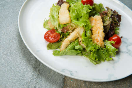 Close-up of Chicken Tempura Salad served on white marble plate. Meat Dish with deep fried chicken strips, lettuce salad mix and cherry tomatoes on stone anthracite background. Asian, American cuisine