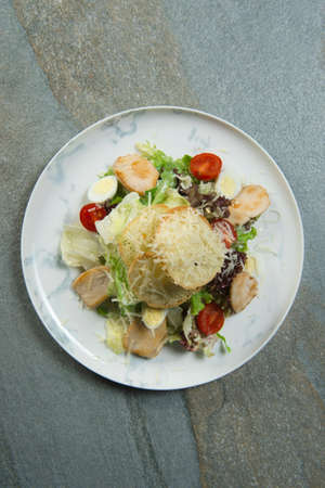 Top view of Traditional Italian Caesar salad served on marble plate. Salad with bread croutons, grilled chicken fillet slices, fresh lettuce, quail eggs, cherry tomatoes on stone background. Flat lay