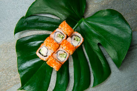 Top view of Japanese sushi roll with Tobiko flying fish roe on top served on tropical monstera leaf on stone background Smoked chicken, Cucumber and cream cheese wrapped in rice and nori seaweed Reklamní fotografie
