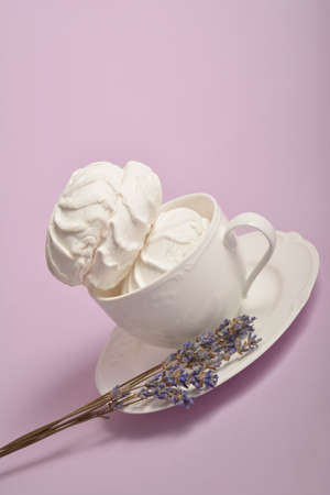 Two Pieces of souffle inside cup on white plate with dry lavender herbs on pastel background. airy dessert zefir (zephyr) made of organic pectin and egg whites, similarly to marshmallow and meringue