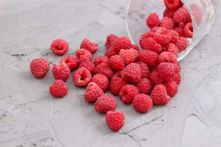 ripe juicy raspberry crumbled out of a glass. forest or garden berries are a bunch on the table. Close up heap of fresh garden harvest on abstract gray concrete background