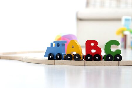 letters of alphabet train on rails in children's playroom. steam train, colorful wagons; wooden toy made of natural eco-friendly material. early childhood development, learning to read, pre-school and child's play concept 写真素材 - 131662507