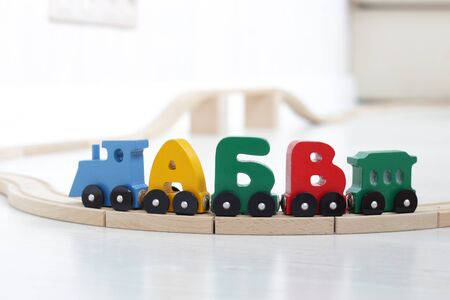 wooden letters of alphabet train on rails in children's playroom. steam train, colorful wagons; wooden toy made of natural, eco-friendly material. early childhood development, learning to read, pre-school and child's play concept 写真素材 - 131660901