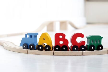 wooden letters of alphabet train on rails in children's playroom. steam train, colorful wagons; wooden toy made of natural, eco-friendly material. early childhood development, learning to read, pre-school and child's play concept