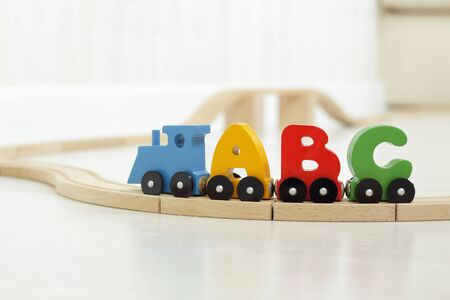 wooden letters of alphabet train on rails in children's playroom. steam train, colorful wagons; wooden toy made of natural, eco-friendly material. early childhood development, learning to read, pre-school and child's play concept 写真素材 - 131660799