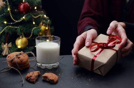 young european woman holds new year gift with red ribbon. A glass of milk and cookies with chocolate and crumbs for Santa on the background of a decorated Christmas tree