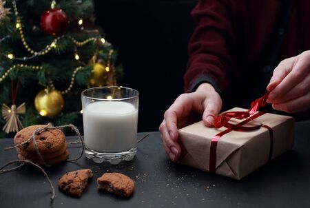 young European woman unwraps Christmas gift with red ribbon. A glass of milk and cookies with chocolate and crumbs for Santa on the background of a decorated Christmas tree