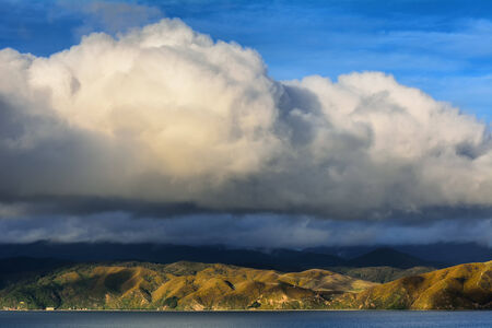 Cumulus clouds over coastal mountains. New Zealand. Stock Photo