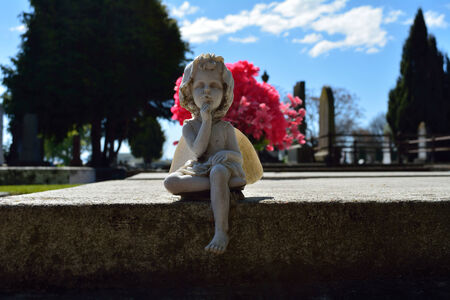 Young angel at grave site in front of flowers