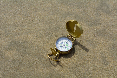 Compass on sand from above.