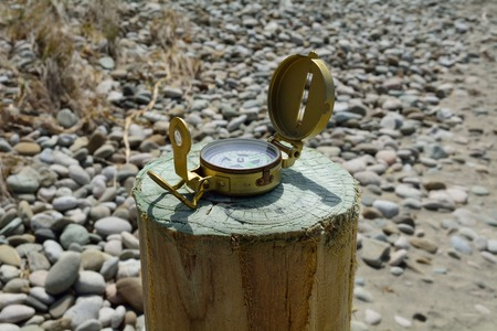Compass on a wooden pole at the beach.