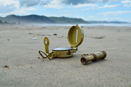 Compass and spyglass on the beach Stockfoto
