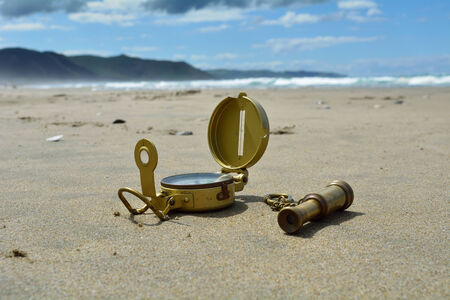 Compass and spyglass on the beach Stock Photo