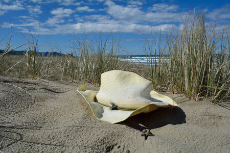 Old hat laying in the sand on a beach.