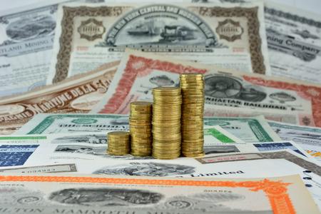 Money on old stock certificates. Stock Photo