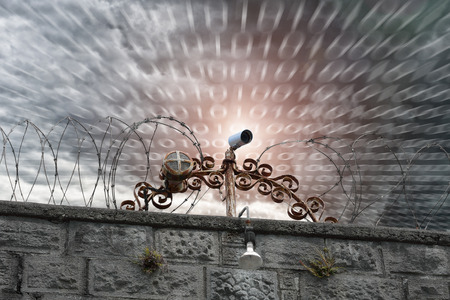 Security camera on a stone wall, protected by barbed wire.