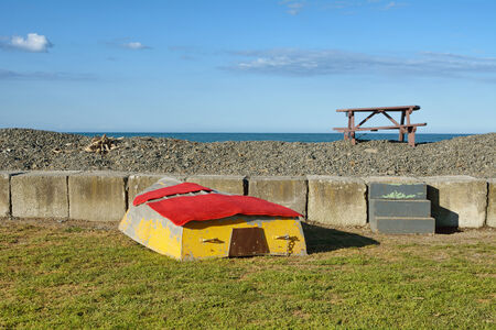 Sea wall with boat and picnic table at the ocean.