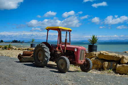 Old tractor by the sea wall in Clifton , New Zealand