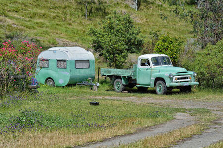 Old Vintage camper and truck on a rural road Stock Photo