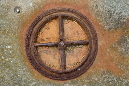 Old rusted iron  wheel,  pipe in concrete