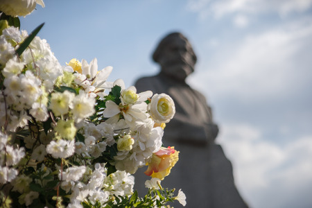 karl: Artificial white and yellow flowers against a monument to Karl Marx during Moscow spring festival
