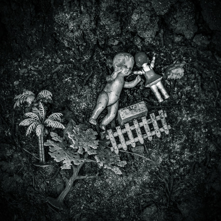 forlorn: Two old dirty dolls and other toys lying on the ground, black and white version