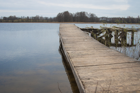 Posts of a broken pier leading out into calm blue tranquil water Banco de Imagens