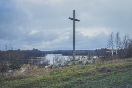 Peasant wooden cross on the mountain near the river bank, lake. The Catholic cross. The Crucifixion.