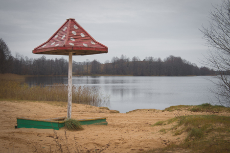 Beach wooden umbrellas on the beach with a red roof. Autumn. Mainly cloudy Imagens - 106175248