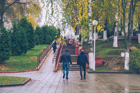 People in the autumn park on the stairs. Men and women