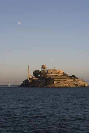 environmentalism: Full moon (daytime), rising over Alcatraz with deep blue water in the foreground.  In the background is the bay bridge. Stock Photo