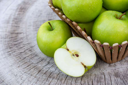 Green granny smith apple in wooden basket on wood table background. Top view. Copy space for text. Standard-Bild
