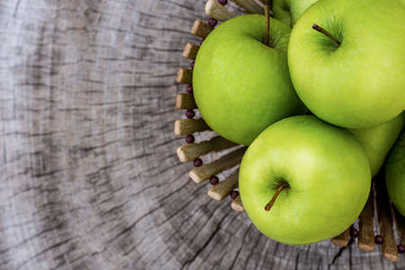 Green granny smith apple in wooden basket on wood table background. Top view. Copy space for text. Standard-Bild - 151418994