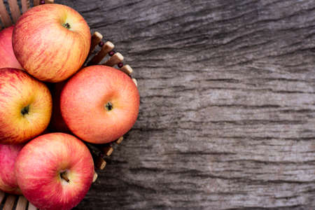 Ripe pink fuji apples in wooden basket on wood table background. Top view.