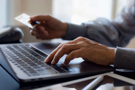 Woman hand typing on laptop computer keyboard and holding credit card for online shopping and internet banking. Online banking, e commerce, e business concept.