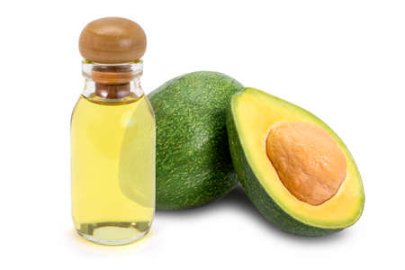 Glass bottle of yellow essential oil extract with whole and half slice of avocado fruit isolated on white background.