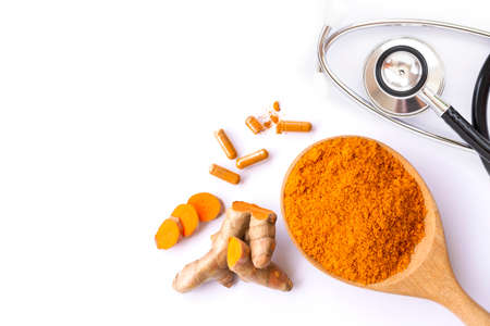 Turmeric powder in wooden spoon, tumeric root, curcumin capsule and isolated white background. Top view. Flat lay.