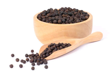 Closeup black pepper seeds or peppercorns ( dried seeds of piper nigrum, piperine ) in wooden bowl and scoop isolated on white background.