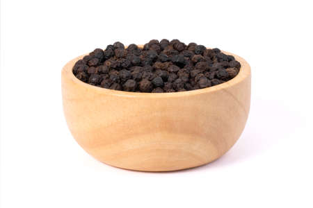 Closeup black pepper seeds or peppercorns ( dried seeds of piper nigrum) in wooden bowl isolated on white background.