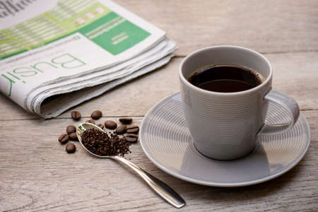 Gray cup of coffee with granulated instant coffee powder in stainless tea spoon with beans and newspaper on wood table background.
