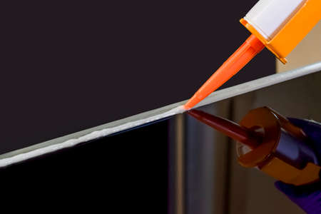 Closeup image of Applying silicone sealant by Caulking gun ,silicon adhesive at dark mirror glass table with reflection. Maintenance concept. Foto de archivo