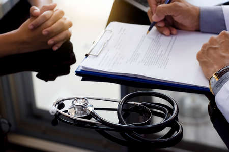 Male medical doctor or physician writing information on clipboard data chart while discussing with patient in medical room at office in clinic or hospital. General medical service concept Standard-Bild