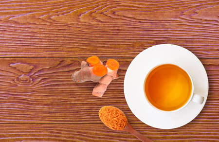 Closeup ceramic cup of hot Turmeric tea with slice and tumeric powder in wooden spoon isolated on wood table background. Healthy drinks and health food boost immune system concept. Top view. Flat lay