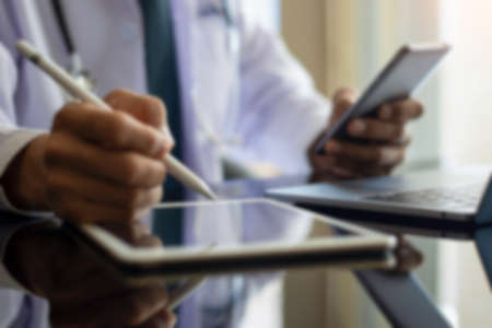 Blurred image of male doctor or business man hand holding and using mobile smart phone and work on digital tablet with laptop computer on the desk at office. Medical networking, online working concept Archivio Fotografico