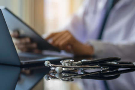 Male doctor in white lab coat hand holding and using modern digital tablet, work on laptop computer with  stethoscope on the desk at workplace. Medic tech,e health, online medical or ehr concept.