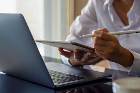 Young asian woman hand holding electronic or stylus pencil and using digital tablet, work on laptop computer with cup of coffee on the desk at home. Online learning, home school, work at home concept.